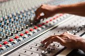 stock photo of mixer  - An expert adjusting audio mixing console at studio