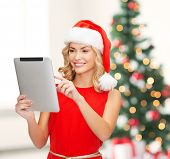 christmas, x-mas, electronics, gadget concept - smiling woman in santa helper hat with tablet pc