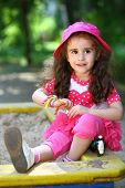 Portrait of a little girl in a pink hat sitting in the sandbox