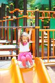 Little girl holds on to the railing to roll down hill on the playground