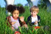 Little girl and boy sitting pensively in the tall grass