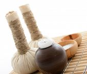 spa still life with spa herbal balls, candlestick and salt in wooden bowl over white