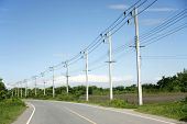stock photo of utility pole  - row of wire pole side road on countryside withe blue sky - JPG