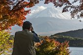 MOUNT FUJI - NOVEMBER 7: A man photographs Mount Fuji through fall foliage November 7, 2012 in Mount Fuji, JP. Viewing of seasonal foliage has been a popular past time in Japan for centuries.