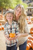 Attractive Mother and Son Portrait in a Rustic Ranch Setting at the Pumpkin Patch.