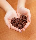 picture of coffee grounds  - Coffee bean in the hand and coffee bean is love heart shape - JPG