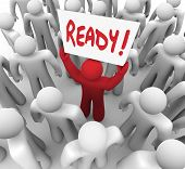 The word Ready on a sign held by a unique red person in a crowd to illustrate being prepared for a t