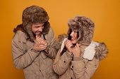 Happy couple in warm winter clothing wearing warm furry caps and jackets laughing as they stand look
