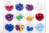 image of molly  - A display of pills in circular containers stacked in rows and columns against a white background - JPG