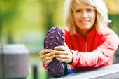 picture of stretching exercises  - Woman runner exercising and stretching autumn nature outdoors - JPG