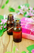 picture of honeysuckle  - Two bottles of aromatic oil pink homemade soap branches with leaves and pink flowers of honeysuckle on a background of wooden boards - JPG