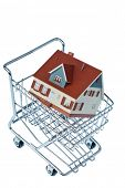 a model of a house in a shopping cart. photo icon for house purchase.