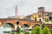 Ponte di Pietra bridge in Verona at foggy morning, Italy