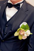green orchid wedding boutonniere on suit of groom