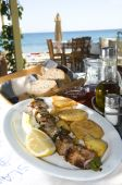 pic of souvlaki  - greek island taverna restaurant specialty pork souvlaki shish kebob with home made wine and crusty bread in greece