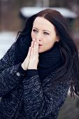 stock photo of shivering  - Shivering woman rubbing hands together to keep her warm - JPG