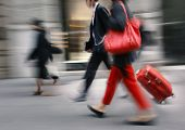image of pedestrians  - People with a red bag and a suitcase walking down the street - JPG