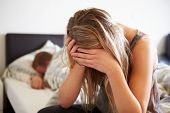 Worried Teenage Girl In Bedroom With Boyfriend