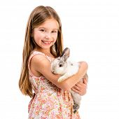 cute smiling girl in a summer dress with a baby rabbit