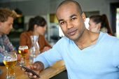 Man sitting at snack bar table checking messages