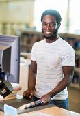 Portrait of happy male librarian scanning books at counter in library