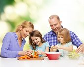 food, family, children, hapiness and people concept - happy family with two kids making dinner at home