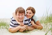 Young Happy Couple In Love Having Fun On Sand Dunes Of The Beach Of North Sea.