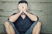 stock photo of tragic  - Depressed young man sitting on the floor and covering his face with a grunge wall background - JPG