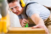 stock photo of workplace safety  - Carpenter working on an electric buzz saw cutting some boards - JPG
