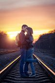 Romantic Couple Kissing At Sunset On Railroad