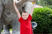 stock photo of tusks  - Boy hanging on an elephant tusks sculpture - JPG