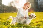 foto of caress  - Little girl caress with her puppy dog in the park - JPG