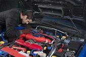 stock photo of muscle-car  - Car repairman examining modified rally car - JPG