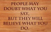 People may doubt what you say, but they will believe what you do - motivational quote by Lewis Cass on wooden red oak background
