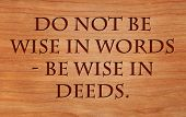 Do not be wise in words - be wise in deeds - motivational Jewish Proverb on wooden red oak backgroun