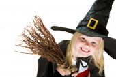 stock photo of warlock  - Portrait of girl in halloween costume and broom smilling at camera - JPG