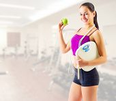 Sporty woman with apple and scales at gym club