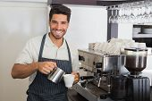 stock photo of waiter  - Portrait of a young waiter smiling and making cup of coffee at coffee shop - JPG