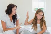 stock photo of stubborn  - Little girl showing stop gesture to angry mother while sitting in bed at home - JPG