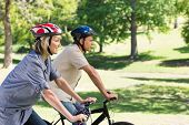 Side view of happy couple cycling in a park