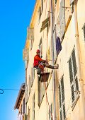 NICE, FRANCE- MARCH 24, 2014: Worker carries severe altitude jobs hanging by a leash on the exterior
