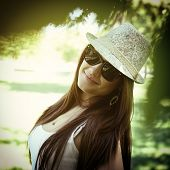 fashion girl outdoor portrait, young woman walking in summer park  in sunglasses and fedora with long brown hair, toned.