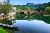 stock photo of arch  - Arched bridge reflected in Crnojevica river Montenegro Balkans - JPG