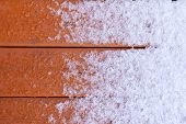 Thawing Fresh Snow On Wooden Deck Planks
