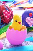 a teddy chick emerging from a hatched pink egg and some easter eggs painted in different colors and