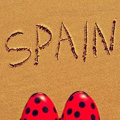 flamenco shoes and the word spain written in the sand of a beach