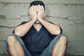 pic of depressed  - Depressed young man sitting on the floor and covering his face with a grunge wall background - JPG