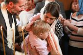Orthodox Priest Performs The Rite Of Baptism