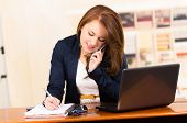 picture of secretary  - portrait of beautiful young secretary working from desk talking on cell phone - JPG