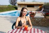 Woman Relaxing With Juice And Straw At Pool